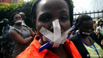 Employees of the Daily Monitor newspaper with their mouths taped shut, take part in a protest against the closure of their premises by the Uganda government, REUTERS/James Akena
