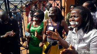 Employees of the Daily Monitor newspaper with their mouths taped shut, sing slogans during a protest against the closure of their premises by the Uganda government, outside their offices in the capital Kampala May 20, 2013. Police raided Uganda's leading independent newspaper on Monday and disabled its printing press after it published a letter about a purported plot to stifle allegations that Uganda President Yoweri Museveni is grooming his son for power, a senior editor said. REUTERS/James Akena (UGANDA - Tags: POLITICS MEDIA CIVIL UNREST)