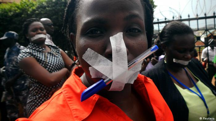 Employees of the Daily Monitor newspaper with their mouths taped shut, take part in a protest against the closure of their premises by the Uganda government, outside their offices in the capital Kampala May 20, 2013. Police raided Uganda's leading independent newspaper on Monday and disabled its printing press after it published a letter about a purported plot to stifle allegations that Uganda President Yoweri Museveni is grooming his son for power, a senior editor said. The pen attached to the tape over the woman's mouth is a reference to the profession of journalism. REUTERS/James Akena (UGANDA - Tags: POLITICS MEDIA CIVIL UNREST)