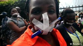 A woman journalist protests with her mouth taped shut