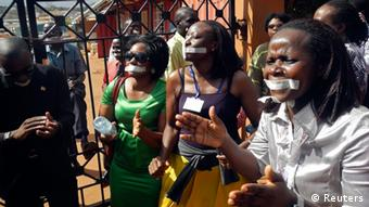 Daily Monitor staff with their mouths taped shut, sing slogans during a protest against the closure of their premises by the Uganda government, outside their offices in the capital Kampala May 20, 2013. Police raided Uganda's leading independent newspaper on Monday and disabled its printing press after it published a letter about a purported plot to stifle allegations that Uganda President Yoweri Museveni is grooming his son for power, a senior editor said. REUTERS/James Akena (UGANDA - Tags: POLITICS MEDIA CIVIL UNREST)