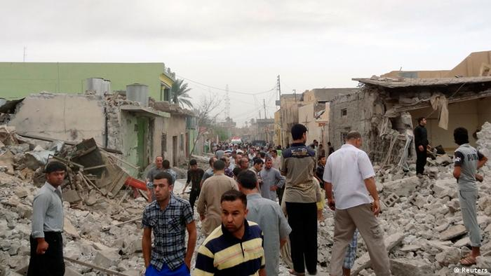 Residents stand amid rubble at blast scene in Tuz Khormatu town in northern Iraq May 21, 2013. Three persons were killed and 52 others were injured after two car bombs were set off in Tuz Khormatu on Tuesday, according to the police. REUTERS/Stringer (IRAQ - Tags: CIVIL UNREST)