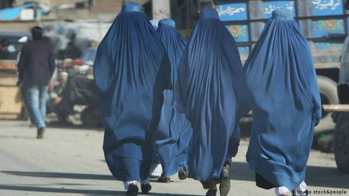 Tri žene u burkama hodaju ulicom, snimljene sleđa