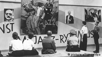 Visitors gaze at an exhibition wall including a riotous depiction of jazz musicians