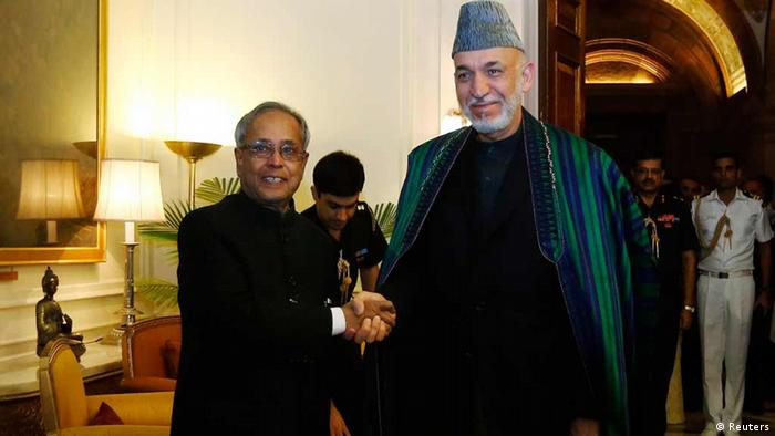 Afghanistan's President Hamid Karzai (R) shakes hands with his Indian counterpart Pranab Mukherjee ahead of their meeting at the Rashtrapati Bhavan presidential palace in New Delhi May 21, 2013. Karzai arrived in India on Monday on a two-day visit. REUTERS/Adnan Abidi (INDIA - Tags: POLITICS)