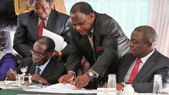 Zimbabwe's Prime Minister Morgan Tsvangirai (R) looks on as President Robert Mugabe signs Zimbabwe's new constitution into law in the capital Harare, May 22, 2013. The constitution, approved overwhelmingly in a referendum in March, clips the powers of the president and imposes a two-term limit. However, it does not apply retroactively so the 89-year-old Mugabe could extend his 33 years in power by another decade. REUTERS/Philimon Bulawayo (ZIMBABWE - Tags: POLITICS)