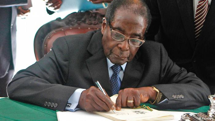 Zimbabwe President Robert Mugabe signs Zimbabwe's new constitution into law in the capital Harare, replacing a 33-year-old document forged in the dying days of British colonial rule and paving the way for elections later this year, May 22, 2013. The constitution, approved overwhelmingly in a referendum in March, clips the powers of the president and imposes a two-term limit. However, it does not apply retroactively so the 89-year-old Mugabe could extend his 33 years in power by another decade. REUTERS/Philimon Bulawayo (ZIMBABWE - Tags: POLITICS)