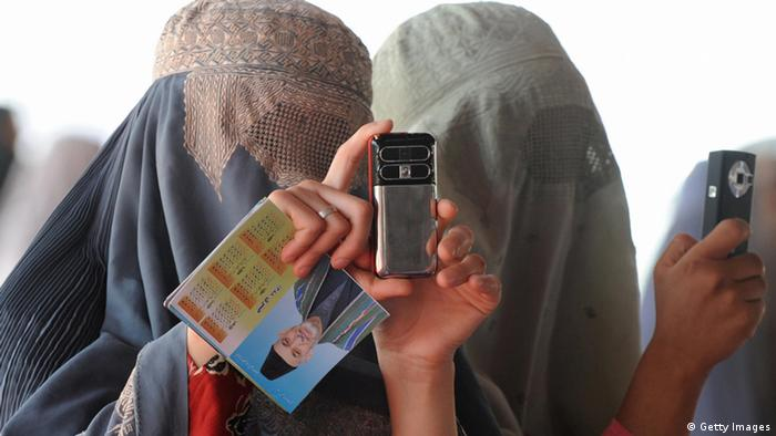 Burqa-clad Afghan women take pictures with their mobile phone at anelection gathering wait for the Afghan President Hamid Karzai in Kandahar on August 16, 2009. Karzai took part August 16 in a live television debate with two of his main rivals running in this week's election, a first for an incumbent head of state in the war-scarred country. AFP PHOTO/Banaras KHAN (Photo credit should read BANARAS KHAN/AFP/Getty Images)