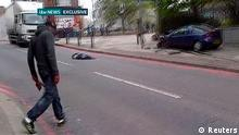 AATTENTION EDITORS - VISUAL COVERAGE OF SCENES OF INJURY OR DEATH A man with bloodied hands and knives walks across a street past the body of a man in a still image from amateur video that shows the immediate aftermath of an attack in which a man was killed in southeast London May 22, 2013. A man was hacked to death in a street near an army barracks in London on Wednesday in what Prime Minister David Cameron said appeared to be a politically motivated attack. MANDATORY CREDIT to ITV News. REUTERS/ITV News via Reuters TV (BRITAIN - Tags: CRIME LAW MILITARY CIVIL UNREST) USE FOR 48 HOURS ONLY. NO SALES. NO ARCHIVES. FOR EDITORIAL USE ONLY. NOT FOR SALE FOR MARKETING OR ADVERTISING CAMPAIGNS. NO ONLINE USE. NOT FOR SALE FOR INTERNET DISPLAY. MANDATORY CREDIT. TEMPLATE OUT