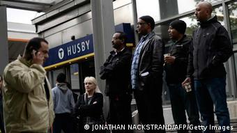 People stand on a street bench next to Husby subway station as they attend a demonstration against police violence and vandalism in the Stockholm suburb of Husby (Photo: AFP PHOTO / JONATHAN NACKSTRAND/DW)