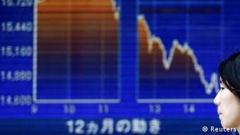 A woman walks past an electronic board displaying a graph showing a dramatic turnaround of Japan's Nikkei average outside a brokerage in Tokyo May 23, 2013. (Photo: REUTERS/Toru Hanai)