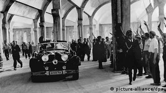 Adolf Hitler wird bei seiner Fahrt im offenen Wagen durch das Wolfsburger Volkswagenwerk von den Arbeitern mit dem Hitlergruß empfangen (undatiert) (Copyright: picture-alliance/dpa)