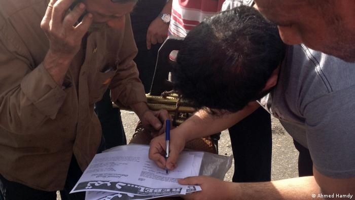 Photo title: A youngman signs tamarod's form