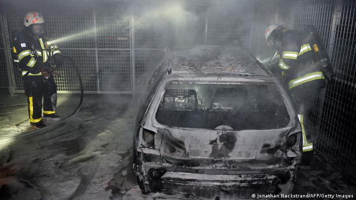 Firemen extinguish a burning car parked in an indoor garage in the Stockholm suburb of Tureberg after youths rioted in several different suburbs (photo via AFP)