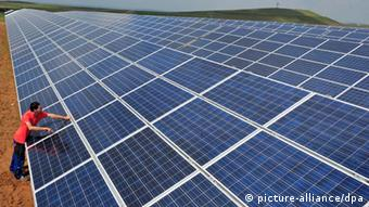 A technician works at a solar farm in Ronneburg, in Germany (Photo: Martin Schutt/dpa)