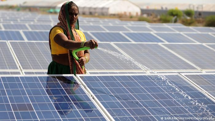 Frau säubert einen Solarpark in Indien (Photo PANTHAKY/AFP/Getty Images)