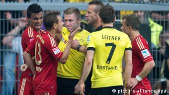 Bayern's Rafinha and Dortmund's Jakub Blaszczykowski, shielded by other players, argue during the two team's last meeting in the Bundesliga, on 04.05.2013 in Dortmund. (Photo: Bernd Thissen/dpa)