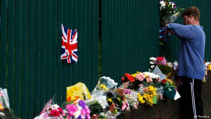 A man leaves a floral tribute for Drummer Lee Rigby, of the British Army's 2nd Battalion The Royal Regiment of Fusiliers, at a security fence outside army barracks near the scene of his killing in Woolwich, southeast London May 24, 2013. Police investigating the murder of the soldier on a busy London street are looking into whether the two suspected killers, British men of Nigerian descent, were part of a wider conspiracy. REUTERS/Luke MacGregor (BRITAIN - Tags: CRIME LAW MILITARY)