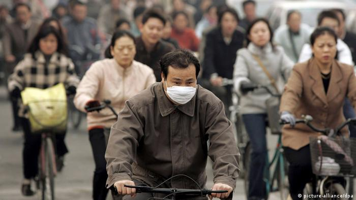 A Chinese man wears a respitory mask while riding a bicycle on a crowded street in Beijing, Thursday 03 November 2005. (Photo: dpa)