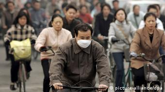 A Chinese man wears a respitory mask while riding a bicycle on a crowded street in Beijing, Thursday 03 November 2005. Next week China will host the Beijing International Renewable Energy Conference 2005 with delegations from around the world. The conference will address the impact of global warming caused by massive consumption of fossil fuels and industrial pollutants. Foto: MICHAEL REYNOLDS +++(c) dpa - Report+++