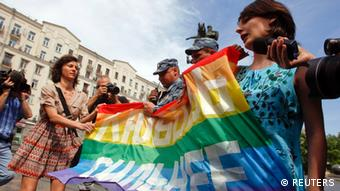 Russian police take away a banner from gay rights activists during a rally outside the mayor's office in Moscow May 25, 2013. The banner reads, Love is stronger. REUTERS/Maxim Shemetov (RUSSIA - Tags: POLITICS CIVIL UNREST)