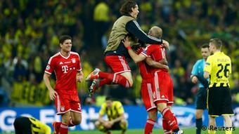 Bayern Munich's players celebrate as dejected Borussia Dortmund players slump onto the grass