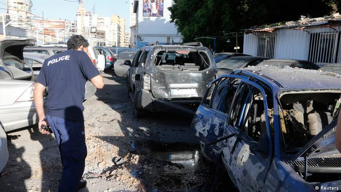 A policeman inspects damaged cars after two rockets hit houses and a car sales yard in Beirut REUTERS/Mohammed Azakir