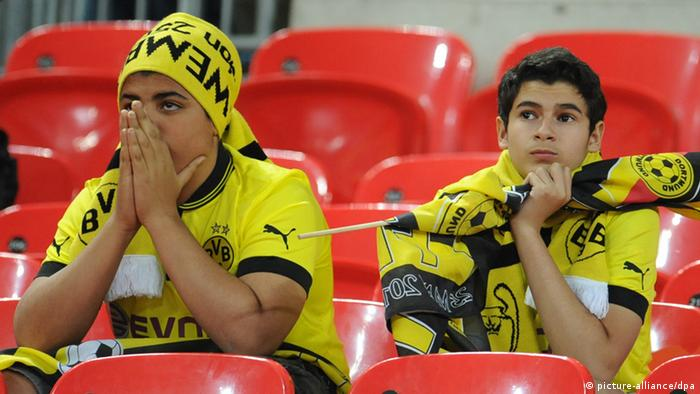 Two fans of Dortmund look dejected after the UEFA soccer Champions League final between Borussia Dortmund and Bayern Munich at Wembley stadium in London, England, 25 May 2013. Photo: Andreas Gebert/dpa