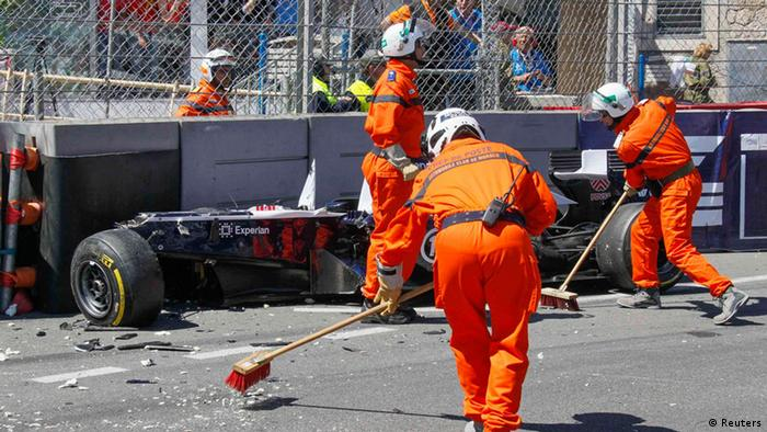 Track marshals clear debris as the car of Williams Formula One driver Pastor Maldonaldo of Venezuela is seen after a crash, during the Monaco F1 Grand Prix May 26, 2013. REUTERS/Robert Pratta