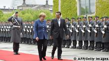 German Chancellor Angela Merkel with Chinese Prime Minister Li Keqiang inspecting a German military honor guard in Berlin