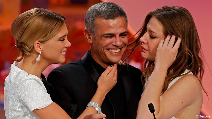 Director Abdellatif Kechiche (C), actresses Lea Seydoux (L) and Adele Exarchopoulos (R) react on stage after he received the Palme d'Or award for the film La Vie D'Adele during the closing ceremony of the 66th Cannes Film Festival in Cannes May 26, 2013. REUTERS/Eric Gaillard (FRANCE