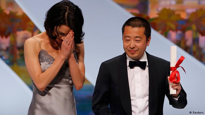 Director Jia Zhangke (R), Best screenplay award winner for the film Tian Zhu Ding (A Touch of Sin), poses on stage next to actress Asia Argento after being awarded during the closing ceremony of the 66th Cannes Film Festival in Cannes May 26, 2013. REUTERS/Eric Gaillard (FRANCE - Tags: ENTERTAINMENT)