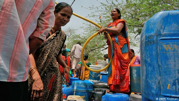 People filling up their plastic canisters from water tanks in Neu Delhi (DW/M. Krishnan)