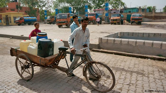People filling up their plastic canisters from water tanks in Neu Delhi