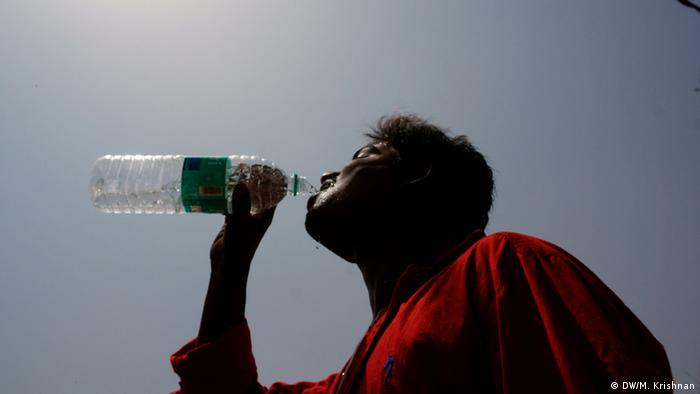 Man drinks water against the sun in New Delhi (Photo: Murali Krishnan / DW)