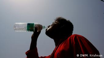 A man drinks from a water bottle (Copyright: DW/Murali Krishnan)
