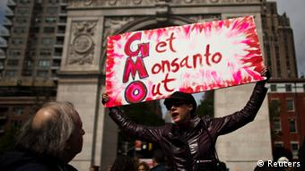 A woman holds up a poster during a protest against U.S.-based Monsanto Co. and genetically modified organisms (GMO), in New York May 25, 2013. Monsanto Co., the world's largest seed company, is pushing on with plans to introduce a controversial new type of herbicide-tolerant crop, setting up 20 field locations around the United States to test and market its Xtend soybean product. REUTERS/Eduardo Munoz (UNITED STATES - Tags: AGRICULTURE FOOD POLITICS CIVIL UNREST BUSINESS)