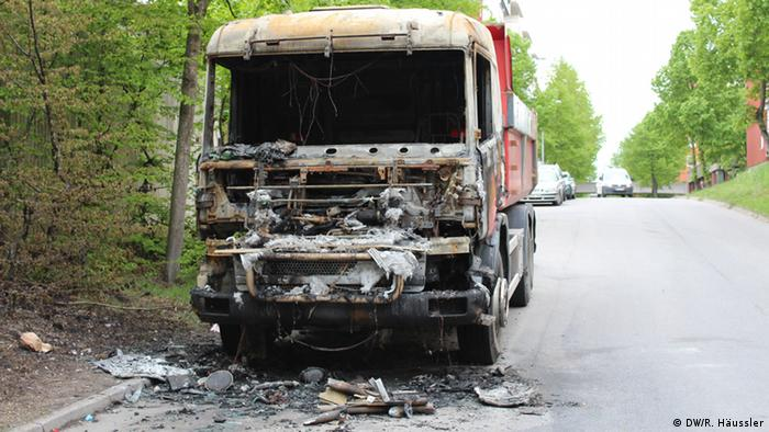 The burned front end of a large van sits on an empty, leafy street in Sweden (Photo: DW/Randi Häussler)