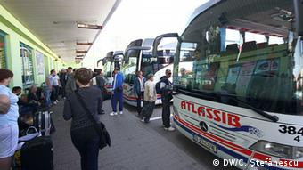 Several people stand next to a white bus (Foto: Cristian Ştefănescu/DW)