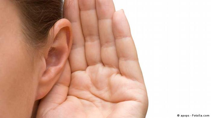 A woman holding her hand to her ear to hear better