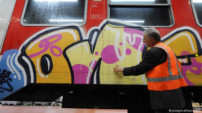 Colorful graffiti on the side of a train as a Deutsche Bahn worker looks on Photo: Fredrik von Erichsen/dpa