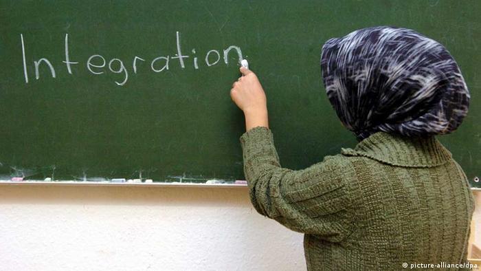 Türkische Frau schreibt das Wort 'Integration' an eine Schultafel (Foto: dpa)