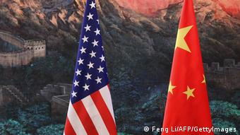 A Chinese man adjusts the Chinese flag before a point press conference by Chinese Foreign Minister Yang Jiechi and US Secretary of State Hillary Clinton at the Great Hall of the People in Beijing on September 5, 2012. Yang said that nations should enjoy freedom of navigation in the South China Sea and promised that there would 'never be issues' in the tense waterway. AFP PHOTO / POOL / Feng Li (Photo credit should read FENG LI/AFP/GettyImages)