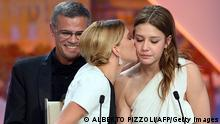 French actress Lea Seydoux (L) kisses on May 26, 2013 fellow actress Adele Exarchopoulos after French-Tunisian director Abdellatif Kechiche (C) won the Palme d'Or for the film Blue is the Warmest Colour during the closing ceremony of the 66th Cannes film festival in Cannes. AFP PHOTO / ALBERTO PIZZOLI (Photo credit should read ALBERTO PIZZOLI/AFP/Getty Images)
