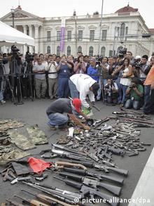 people stand around guns lying on the ground (Foto: Roberto Escobar/EPA)