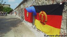 An East Germany flag hangs on the Berlin Wall in 1990