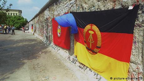An East Germany flag hangs on the Berlin Wall in 1990 (picture-alliance/ZB)