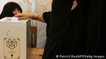 Eine Hand wirft einen Wahlzettel in eine Wahlurne. (Photo credit PATRICK BAZ/AFP/Getty Images)