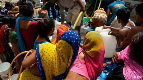Women at a slum fight over water after a tanker delivery (Photo: DW/Murali Krishnan)