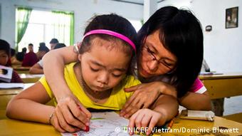 A little Vietnamese girl is drawing on a piece of paper with the help of an adult. (Photo: UNICEF Vietnam/Dominic Blewett)